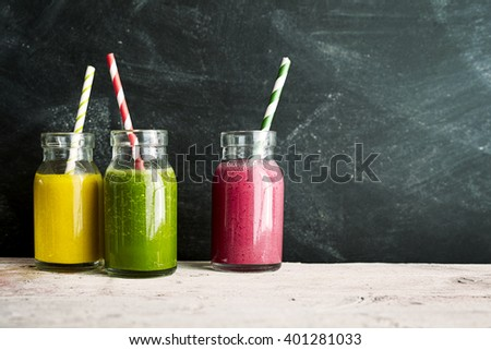 Three mason jars of yellow green and pink tropical fruit drinks with swirl colored straws next to a dusty chalkboard - stock photo