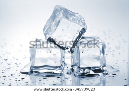 Three melting ice cubes on glass table - stock photo