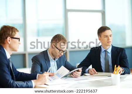 Three men at meeting in office - stock photo