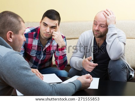 Three men discussing financial issues - stock photo