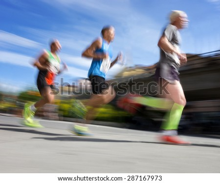 Three men in blurred motion in running competition - stock photo