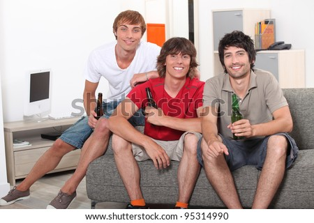 Three men sat on sofa holding bottles of beer - stock photo