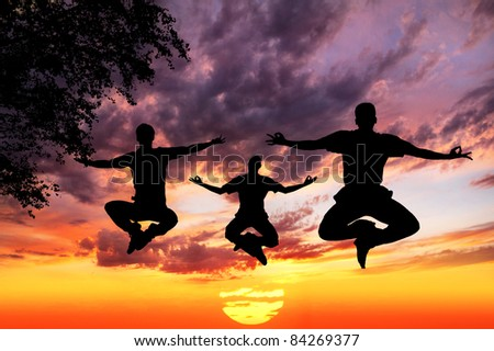 Three Men silhouettes doing yoga padmasana lotus pose in jumping with tree nearby outdoors at sunset background - stock photo