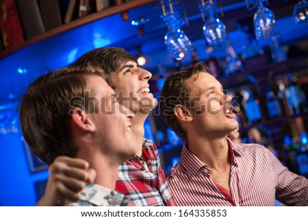 Three men stand in a row embracing smile and look in front of you, sports fans - stock photo