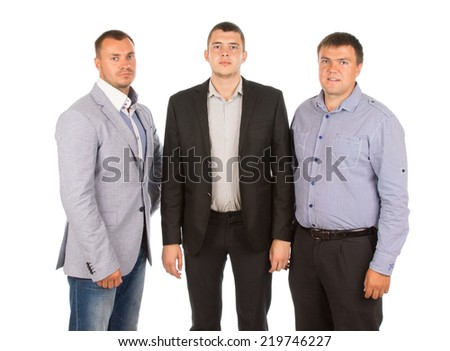 Three men standing side by side in a jacket, suit and shirtsleeves, looking at the camera with serious expressions, three quarter on white - stock photo