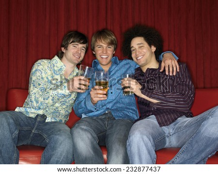 Three Men with Beer Glasses on Sofa - stock photo