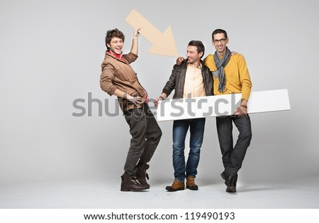 Three men with empty board and arrow - stock photo