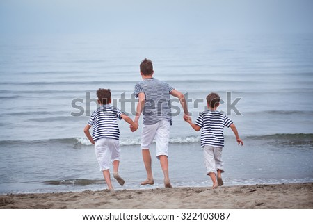 Three merry, happy, brother plays at sea, laughing and squirting water, italy,  - stock photo
