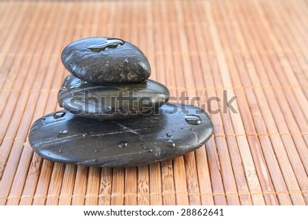 Three message stones stacked on one another with water drops all on a bamboo background. - stock photo
