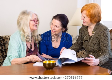 Three Middle Age Women Best Friends Enjoying their Talks at the Living Area While Scanning a Magazine. - stock photo