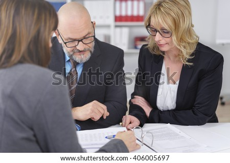 Three middle aged adult business people meeting and discussing information in three ring binder at small office - stock photo