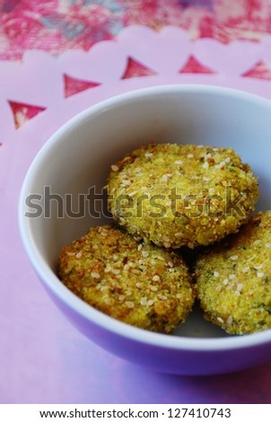 Three millet vegetarian meatballs in a small violet china bowl, pink hearts in background - stock photo