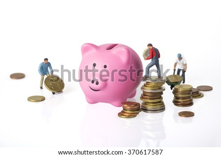 Three Miniature workers, euro coins and piggy bank - stock photo