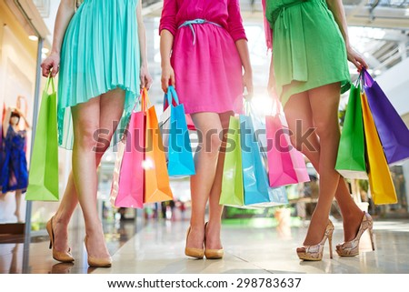 Three modern girls in bright dresses and stylish shoes holding paperbags - stock photo