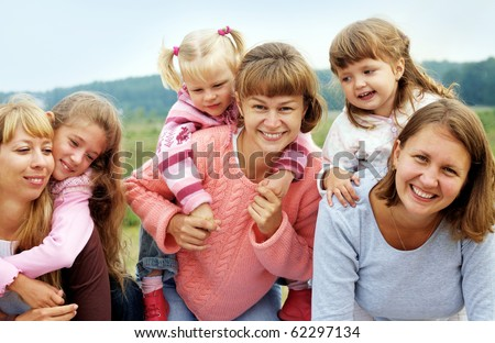 Three mothers have a good time with three daughters outdoors - stock photo