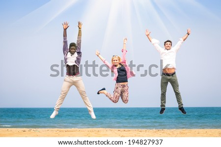 Three multiracial friends jumping at the beach - Concept of happiness and friendship against racism - stock photo