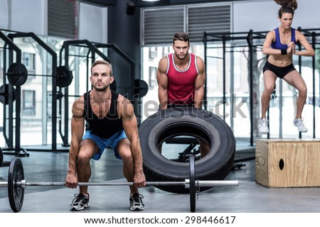 Three muscular athletes lifting and jumping at the crossfit gym - stock photo