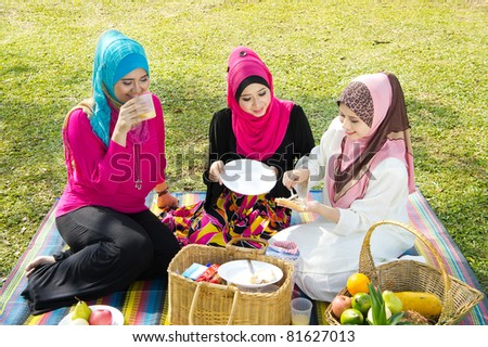 three muslimah girl breakfast at garden - stock photo