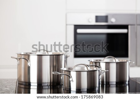 Three new metal pots in the kitchen on induction hob on modern kitchen background - stock photo