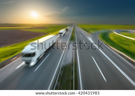 Three new trucks in a row driving fast towards the sun. Speed blurred motion drive on the freeway. Freight scene on the motorway near Belgrade, Serbia. Speed concept. - stock photo
