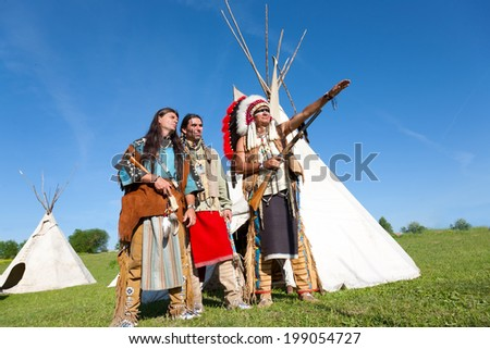 Three North American Indians stand near a wigwam - stock photo