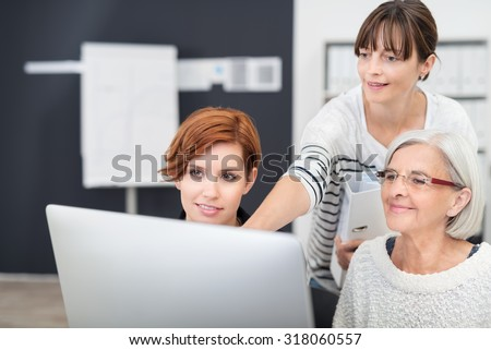 Three Office Women Looking at Computer Screen Together Inside the Workplace. - stock photo