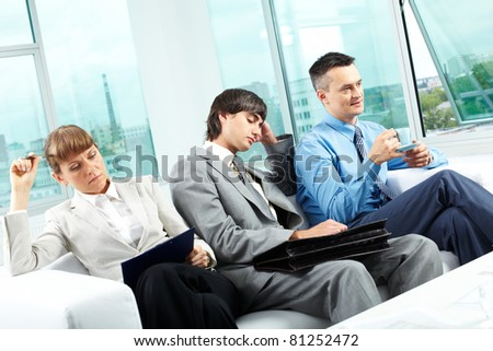 Three office workers sitting on sofa after hard workday - stock photo