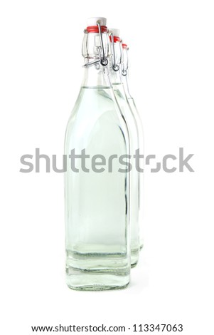 Three old-fashioned glass bottles full of water - stock photo