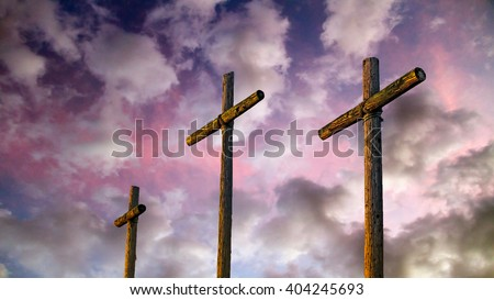 Three old rugged wooden crosses stand tall against an amazing and dramatic sky at sunset. - stock photo