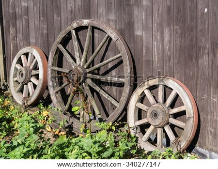 Three old wagon wheels with metal rims leaning against a wall of wooden planks - stock photo