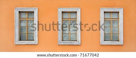 Three old windows on the orange wall - stock photo