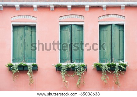 three old windows with shutters and small flowerpots - stock photo