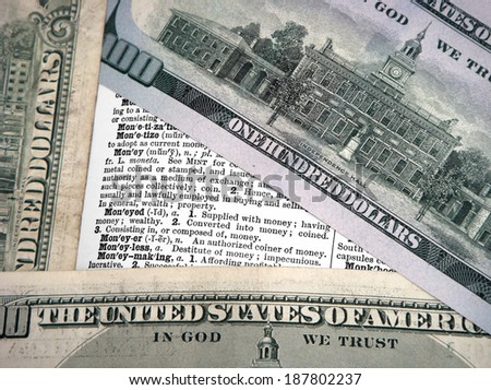 Three One Hundred Dollar Bills Forming A Triangle Around The Meaning Of Money. Cropping of image is close to bring importance to the definitions of this vintage dictionary. - stock photo