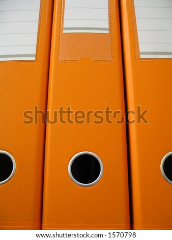 Three orange lever arch folders. - stock photo
