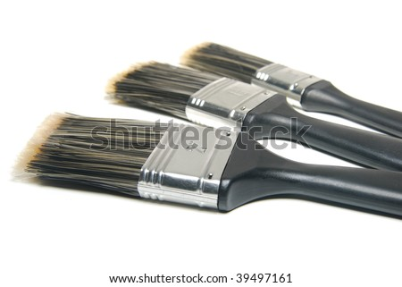 Three paint brushes of different sizes over white - stock photo