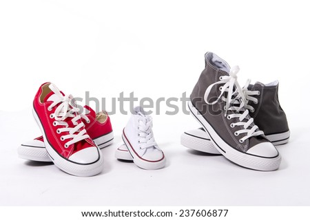 three pair of casual shoes in father big, mother medium and son or daughter small kid size representing family, growth, education and togetherness concept isolated on white background - stock photo