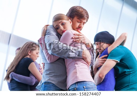 Three pair of people hugging each other. Girl with upset look on the foreground  - stock photo
