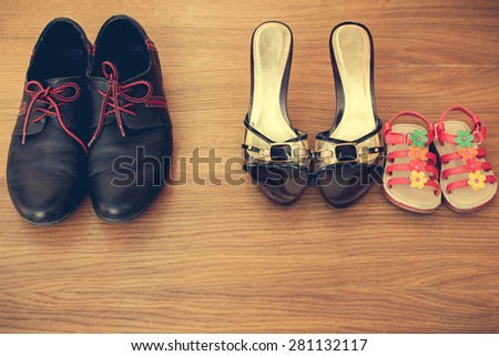 Three pairs of shoes: men, women and children. Baby sandals stand next to women's shoes. concept of the child is friends with his mother. Idea parents divorced, child remained with mother. Toned image - stock photo