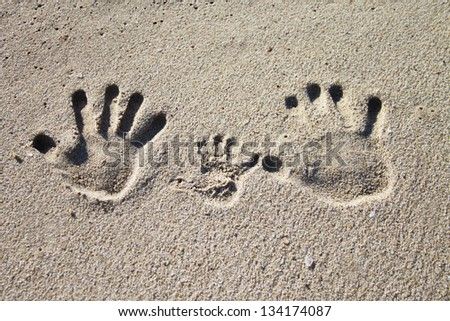 Three palm imprints of family on sand - stock photo