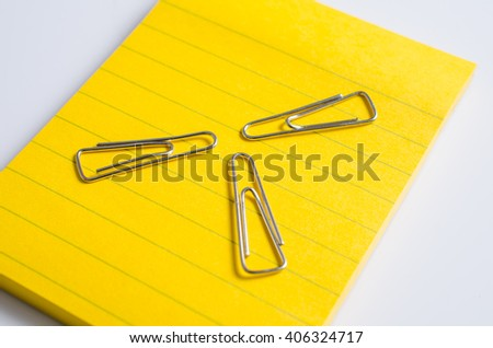 Three paper clip with memo note background - stock photo