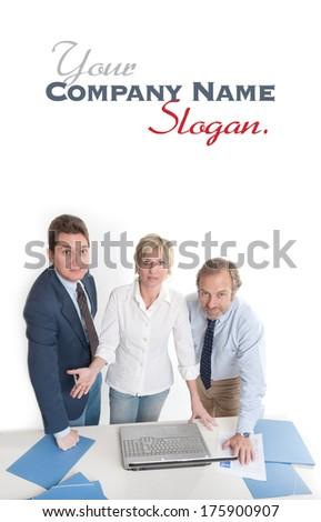 Three people around a laptop looking at the camera  - stock photo