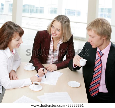 Three people gathered together around the table and discuss ideas at business meeting - stock photo