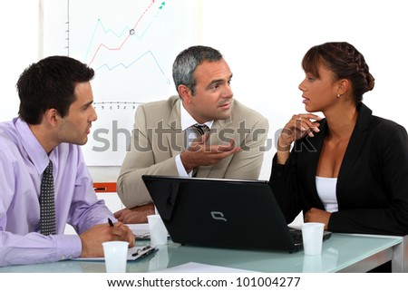 Three people in animated business meeting - stock photo