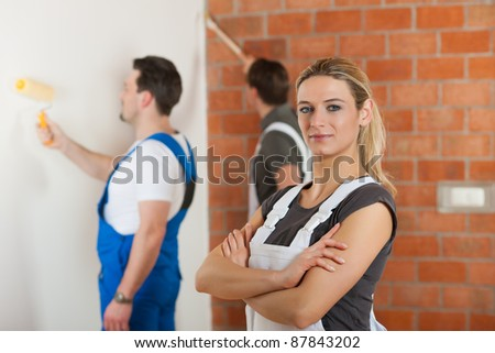 Three people - one woman and two men - renovating an apartment; the woman is standing with arms crossed in front - stock photo