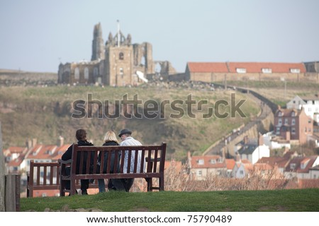 Three people sitting on a bench and looking at an abbey in Whitby - stock photo