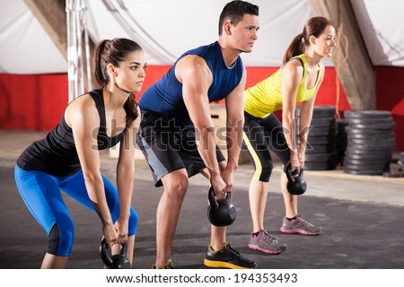 Three people working out with kettlebells in a cross-training gym - stock photo