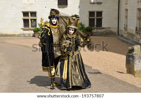 Three persons in Venetian masks and costumes - stock photo