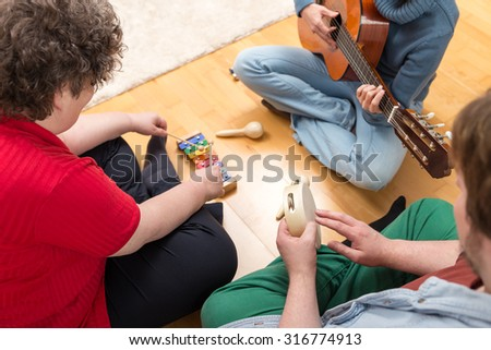 three persons playing sundry instruments at home - stock photo