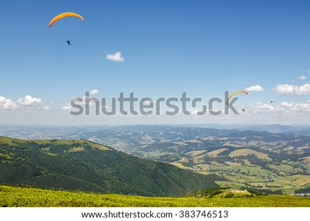 Three persons skydiving  flying over the mountains. parachute extreme sport - stock photo