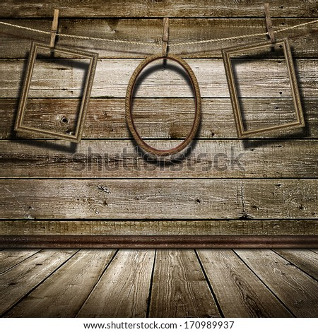 three picture frame hanging on clothespins on a background of of wooden wall - stock photo